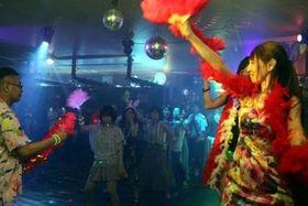 ミラーボールが輝く店内で踊りを楽しむ参加者