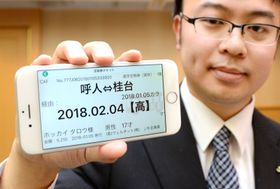 「スマホ定期券」のデモ画面が表示されたスマートフォンを持つJR北海道の社員=17日午後、札幌市