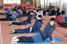 ストレッチで体をほぐす選手=金沢市の県陸上競技場サブグラウンド室内練習場