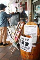 昴珈琲店が店頭の屋台の脇に設けている「樽募金」のたる