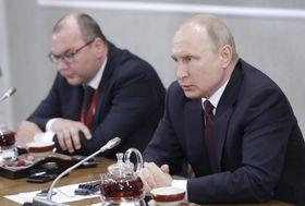 サンクトペテルブルクでの主要通信社幹部との会見で話すプーチン・ロシア大統領(右)=25日(タス=共同)