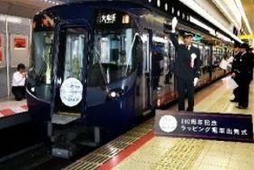西鉄福岡(天神)駅を出発する110周年記念のラッピング電車=25日午前11時半、福岡市・天神