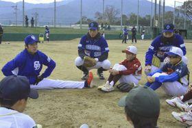 柔軟性の大切さをアドバイスする木下投手(左)=阿波市民球場