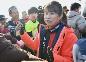 スタート前の10キロの部出場の市民ランナーらをハイタッチで激励する吉田沙保里さん=津市北河路町で