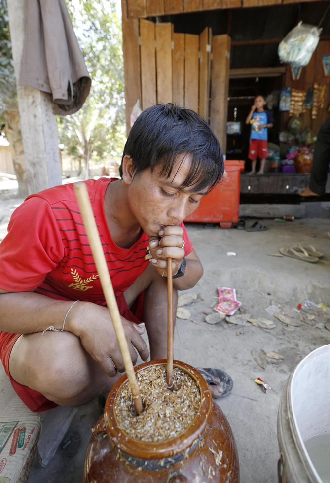 かめに入った酒「スラー・ペアン」を飲む先住民の村人。竹の筒を使って回し飲みする=カンボジア北東部ラタナキリ州・タボー村(撮影・大森裕太、共同)