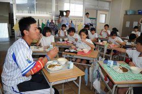 児童と一緒に球団名物のカレーを食べる関根選手