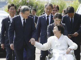 14日、韓国政府主催の慰安婦記念日の式典に出席し、慰安婦だった女性と手をつなぐ文在寅大統領(手前左)=韓国・天安(聯合=共同)