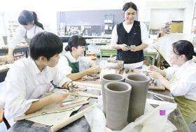 吉野さん(右から2人目)の指導を受けてトロフィー作りに励む基町高の生徒(14日、広島市中区)