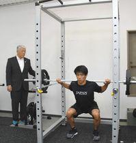 トレーニングを実演する堀島選手(右)を見守る岡崎町長=池田町総合体育館で